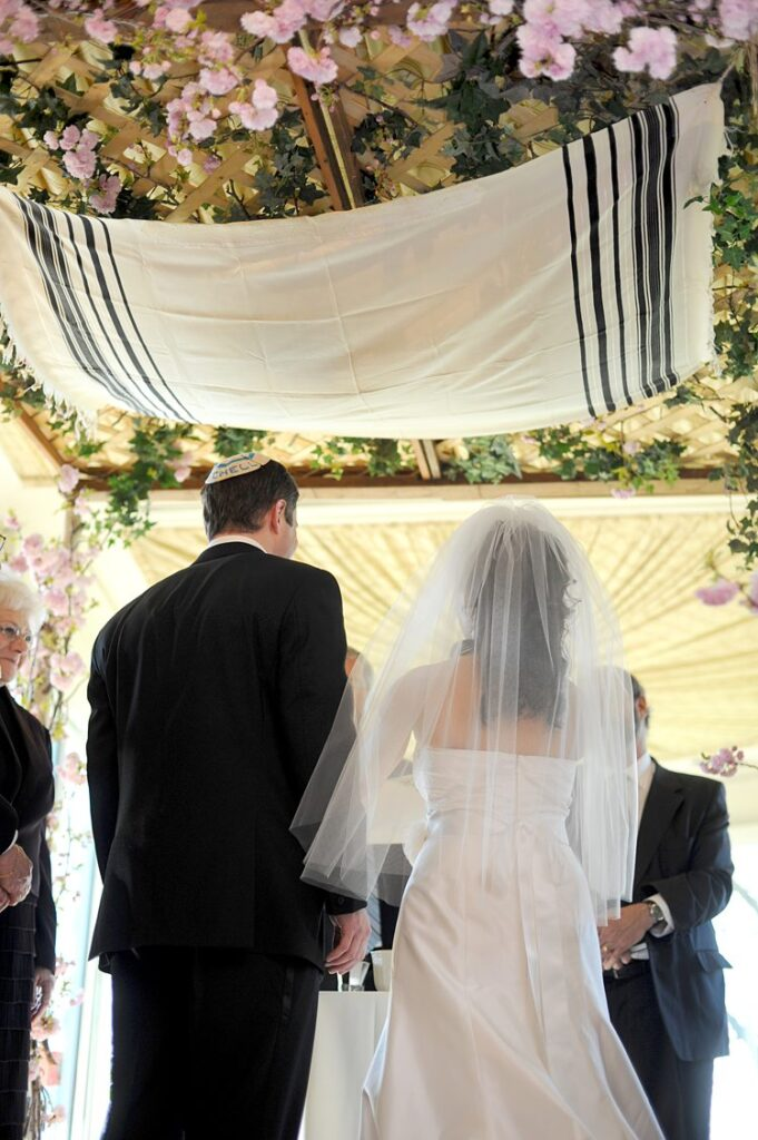 Bride and groom at their Tappan Hill Mansion wedding in Tarrytown, NY under a chuppah.