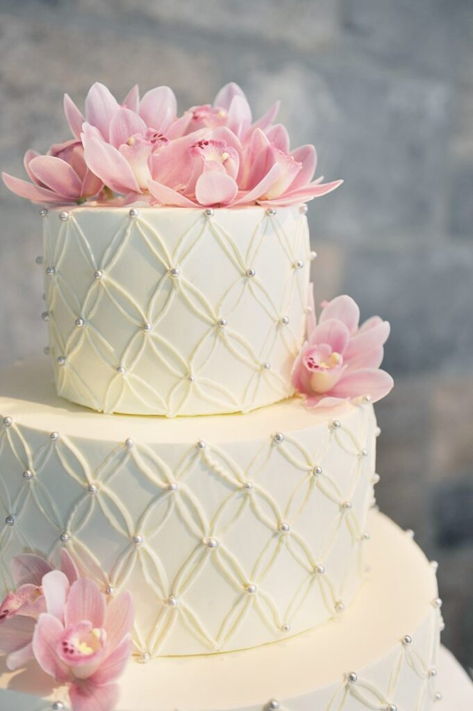 Pink orchids decorating a three-tier buttercream decorated white wedding cake at Tappan Hill Mansion in Tarrytown.