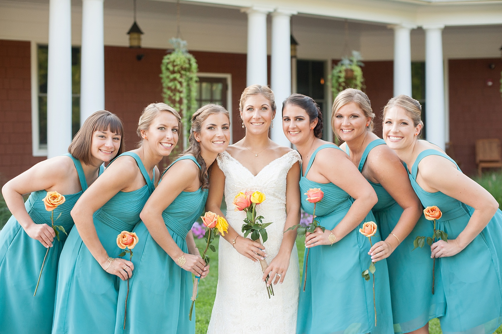 Wedding party in teal dresses and single stem roses for a Hollow Brook Golf Club wedding in New York. Photos by Mikkel Paige Photography.