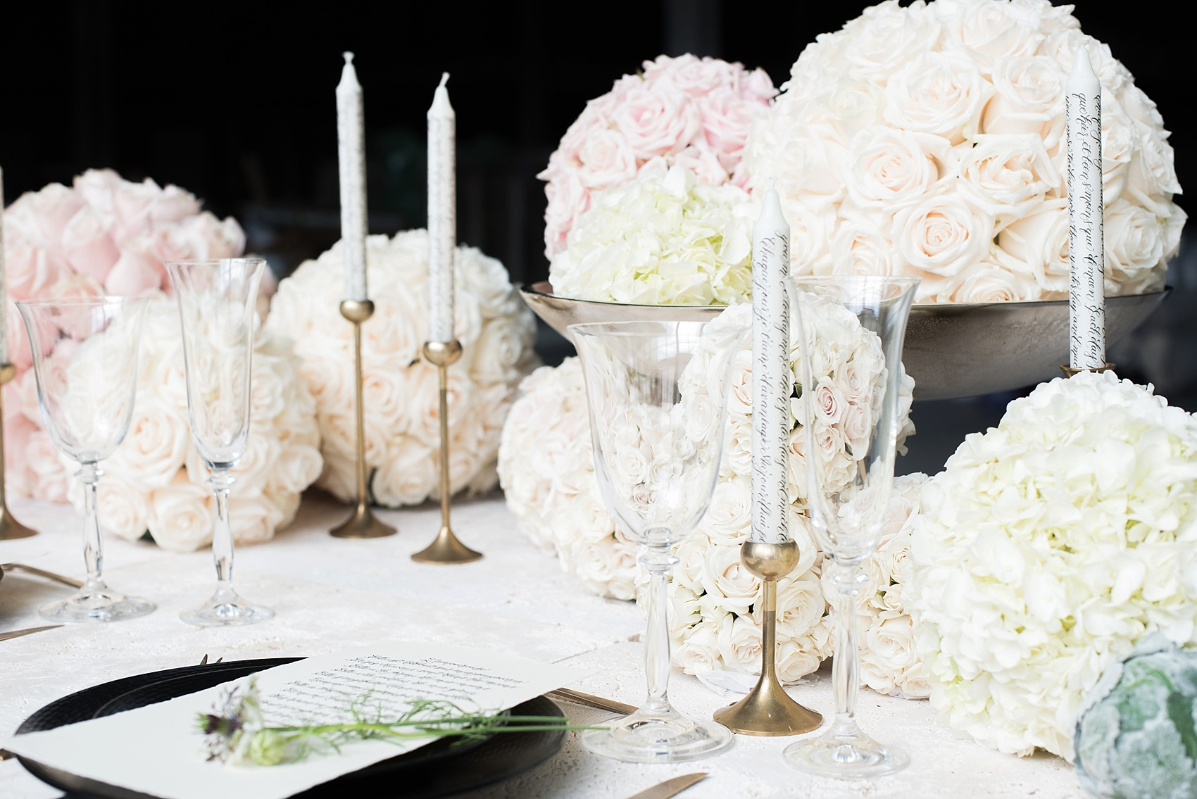 Destination wedding photographer Mikkel Paige captures a glamorous industrial bridal session in Hawaii with Burnett's Boards and Moana Events. White and pink pomander flower spheres adorn the sweetheart table with calligraphy candles.