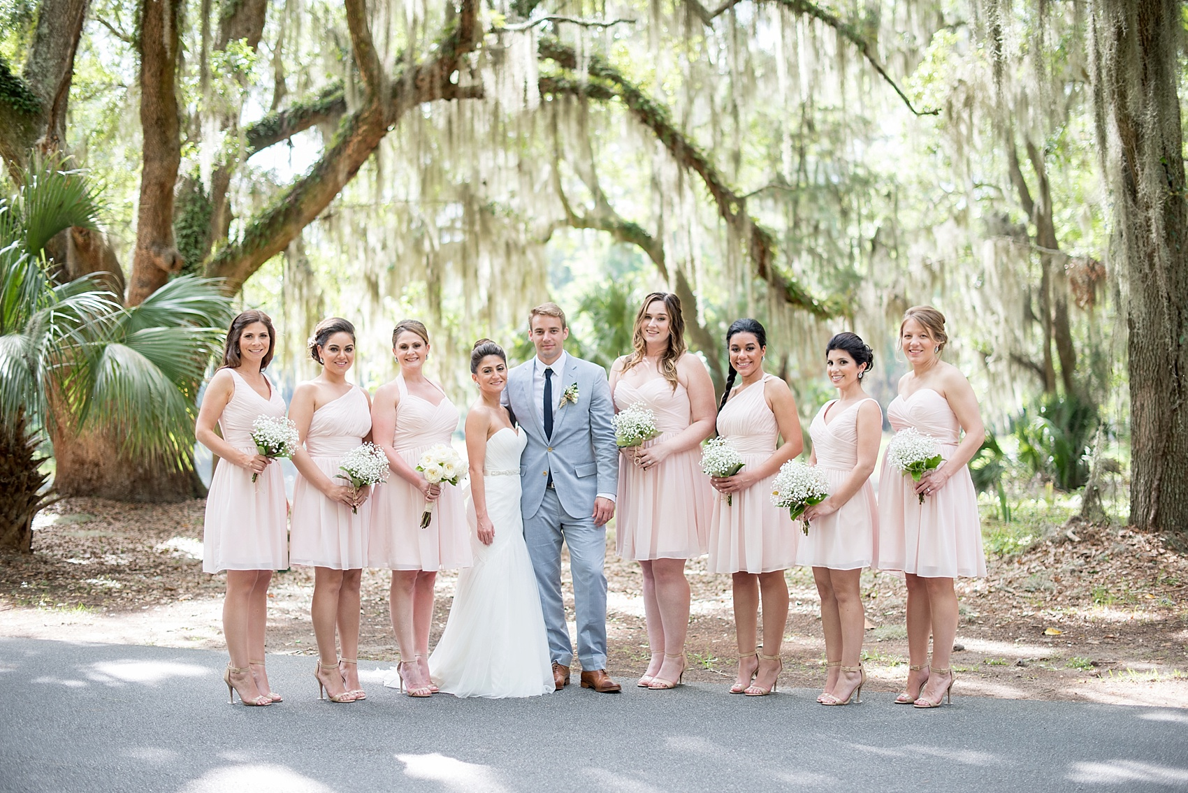 Bridesmaids in short pink Bill Levkoff dresses with Baby's Breath and Magnolia Leaf bouquets. Wedding party at Haig Point, South Carolina, off the coast of Hilton Head. Photos by Mikkel Paige Photography.