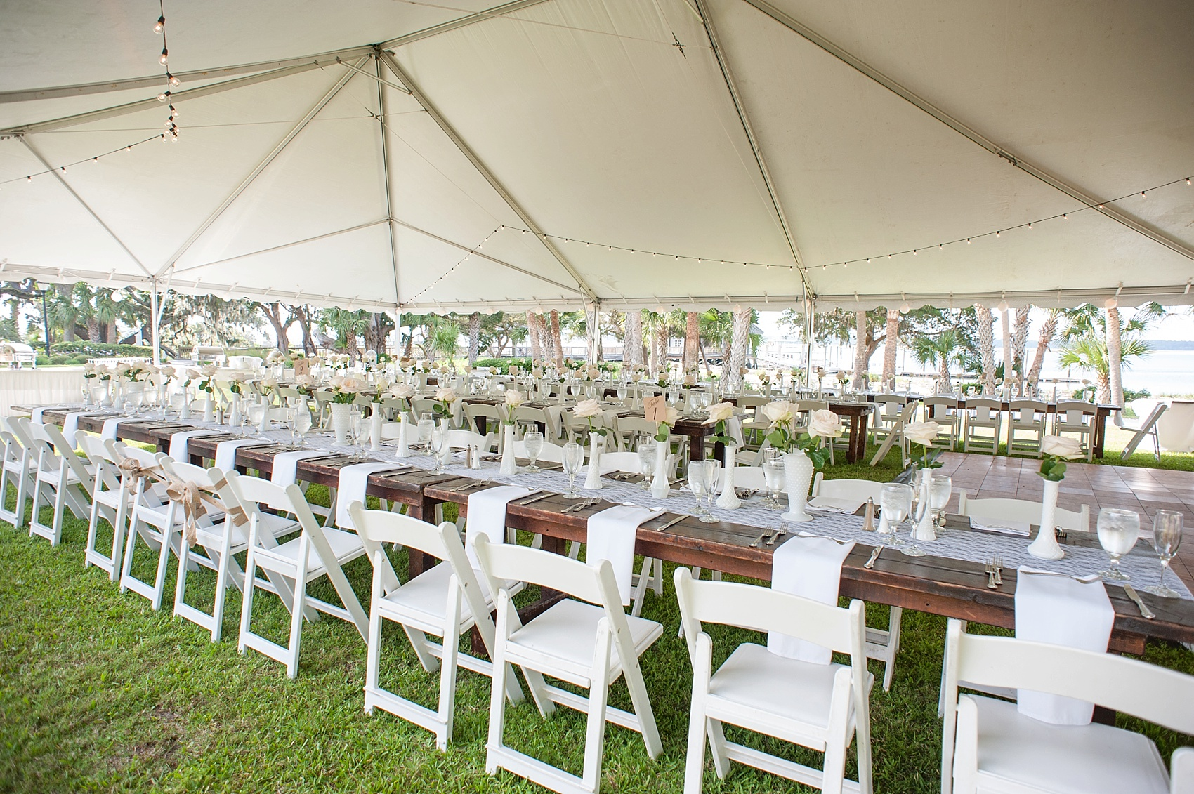 Tented wedding reception for a Haig Point wedding in South Carolina, off the coast of Hilton Head. Farm tables and white roses and vases complete the look. Photos by Mikkel Paige Photography.