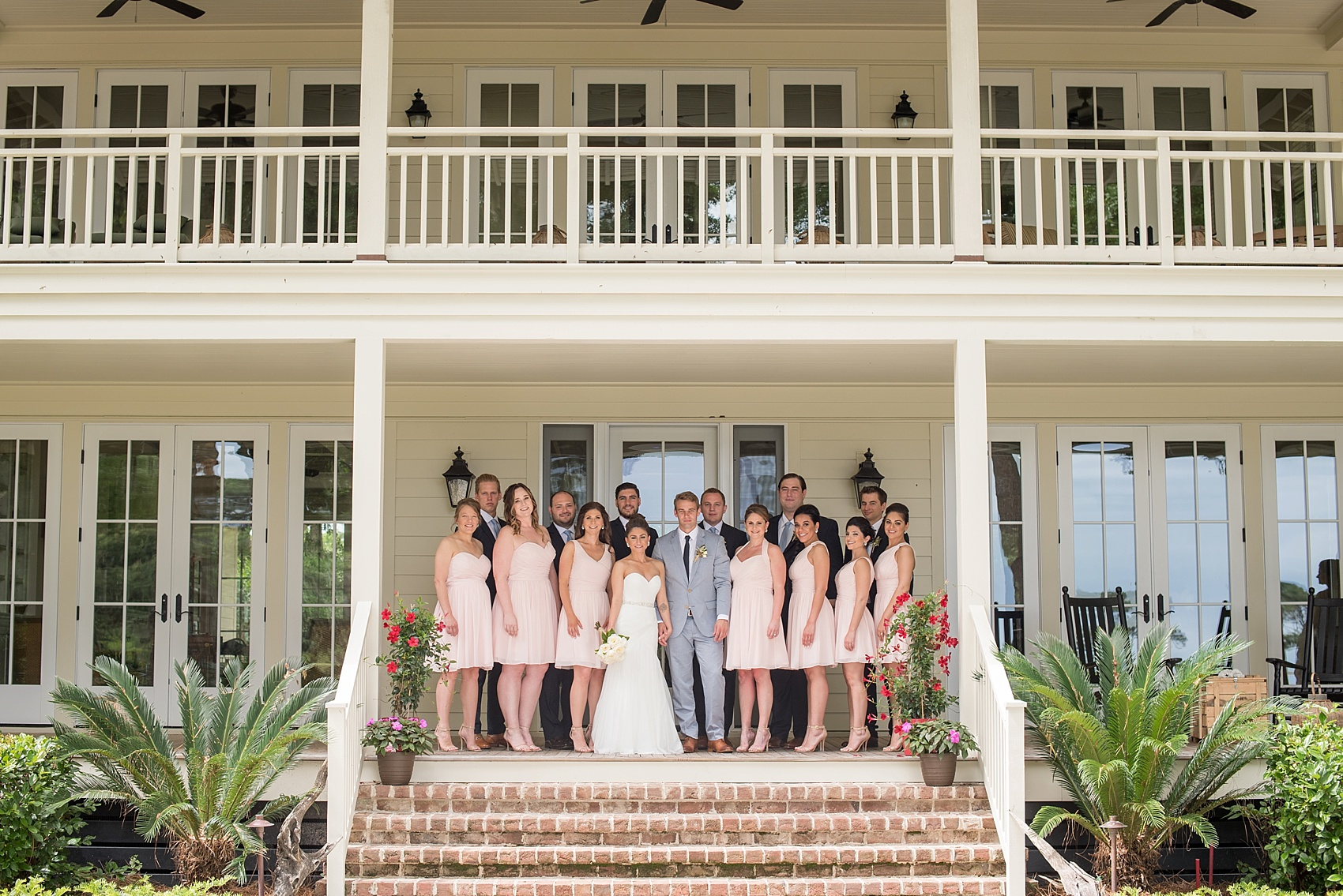 Groomsmen in navy Zara suits and bridesmaids in short pink Bill Levkoff dresses. Wedding party at Haig Point, South Carolina, off the coast of Hilton Head. Photos by Mikkel Paige Photography. Baby's breath bouquets and succulent boutonnieres complete the look.