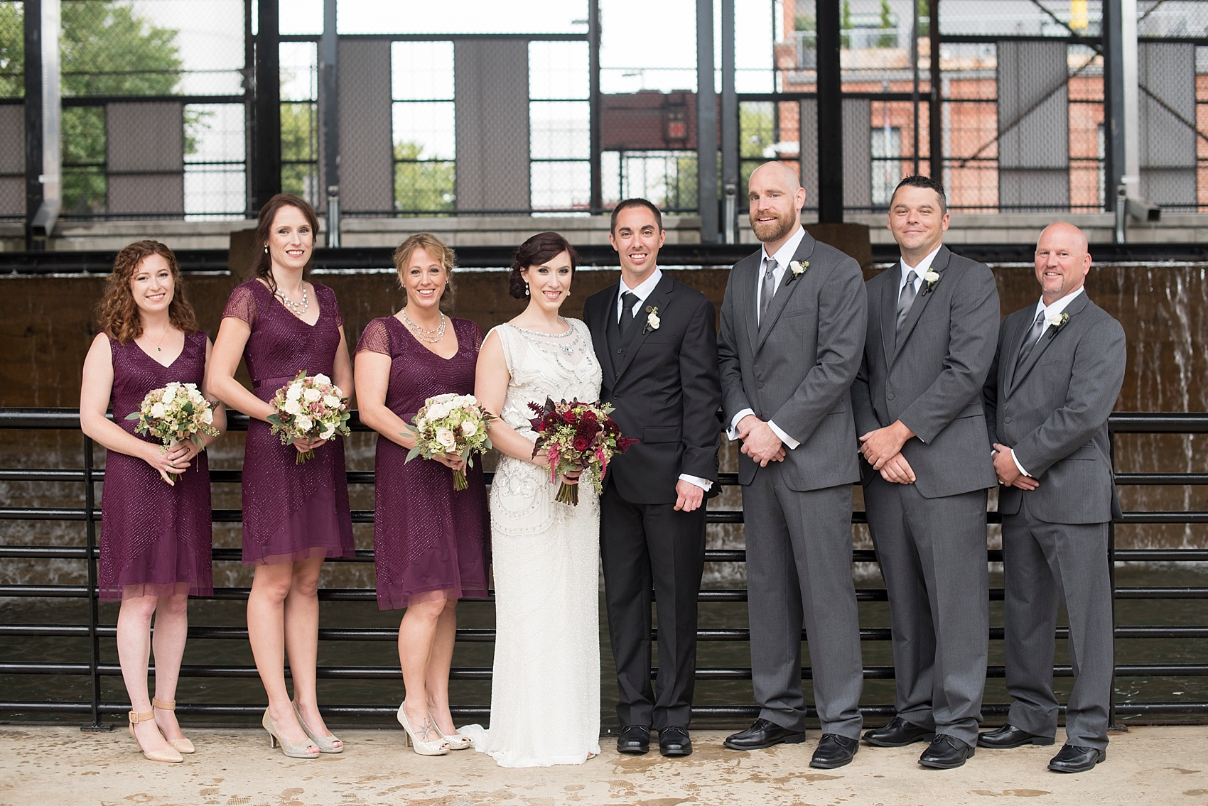 Wedding party photos in the rain! Burgundy bridesmaids with bride in beaded 1920s art deco gown. Bay 7 Durham, NC wedding. Photos by Mikkel Paige Photography.