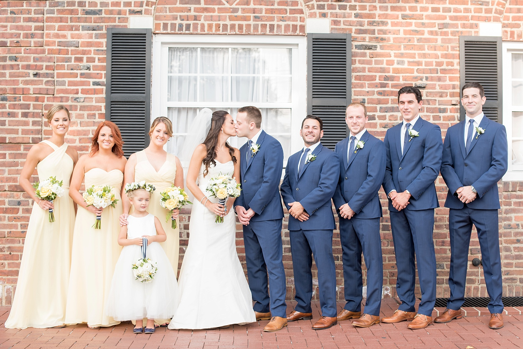 Wedding party in navy blue suits and yellow chiffon dresses for the groomsmen and bridesmaids in New Jersey for this nautical wedding at the Molly Pitcher Inn. Photo by Mikkel Paige Photography.