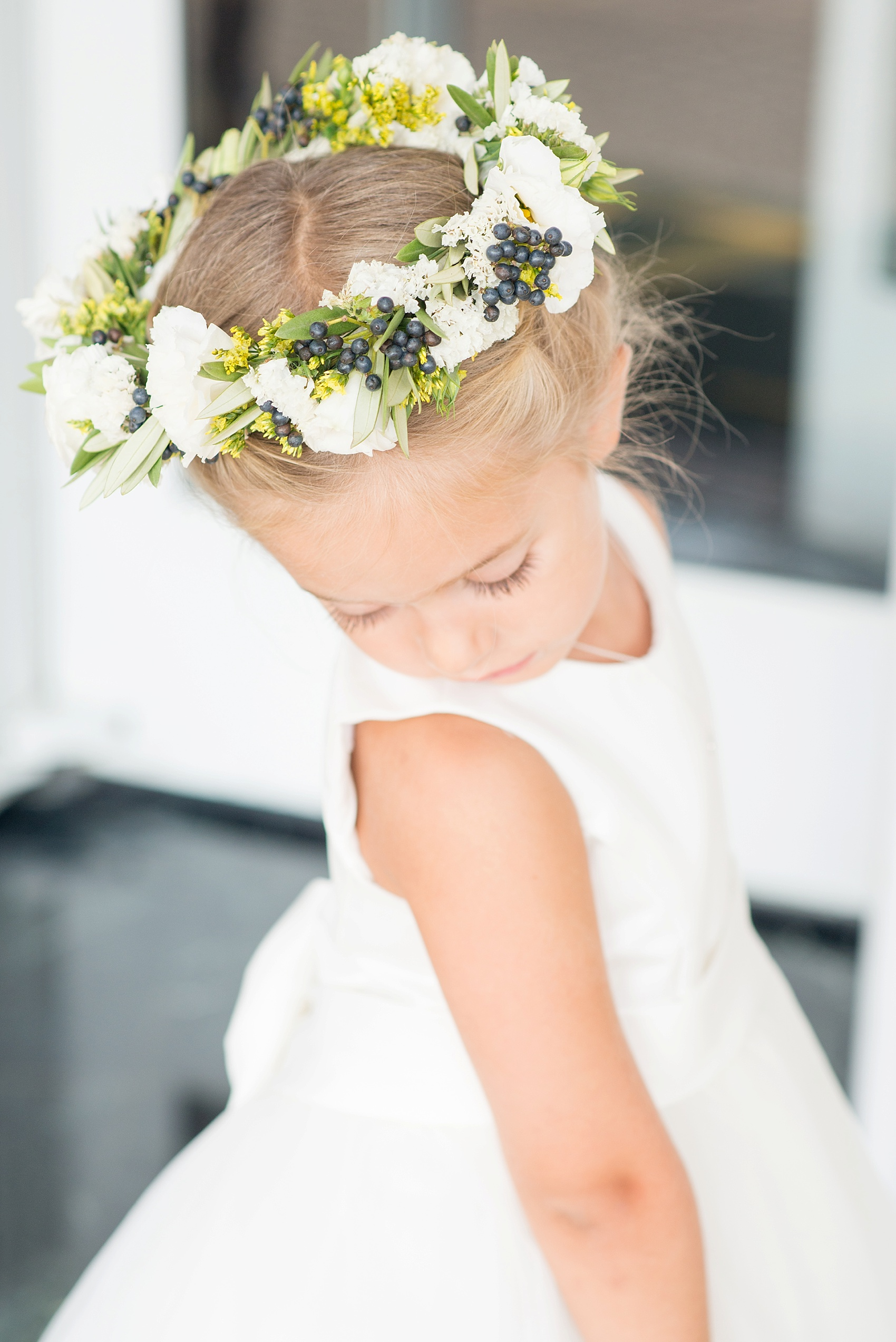 Flower girl in her flower crown of roses, white ranunculus and blue berries in New Jersey for a nautical wedding at the Molly Pitcher Inn. Photo by Mikkel Paige Photography.