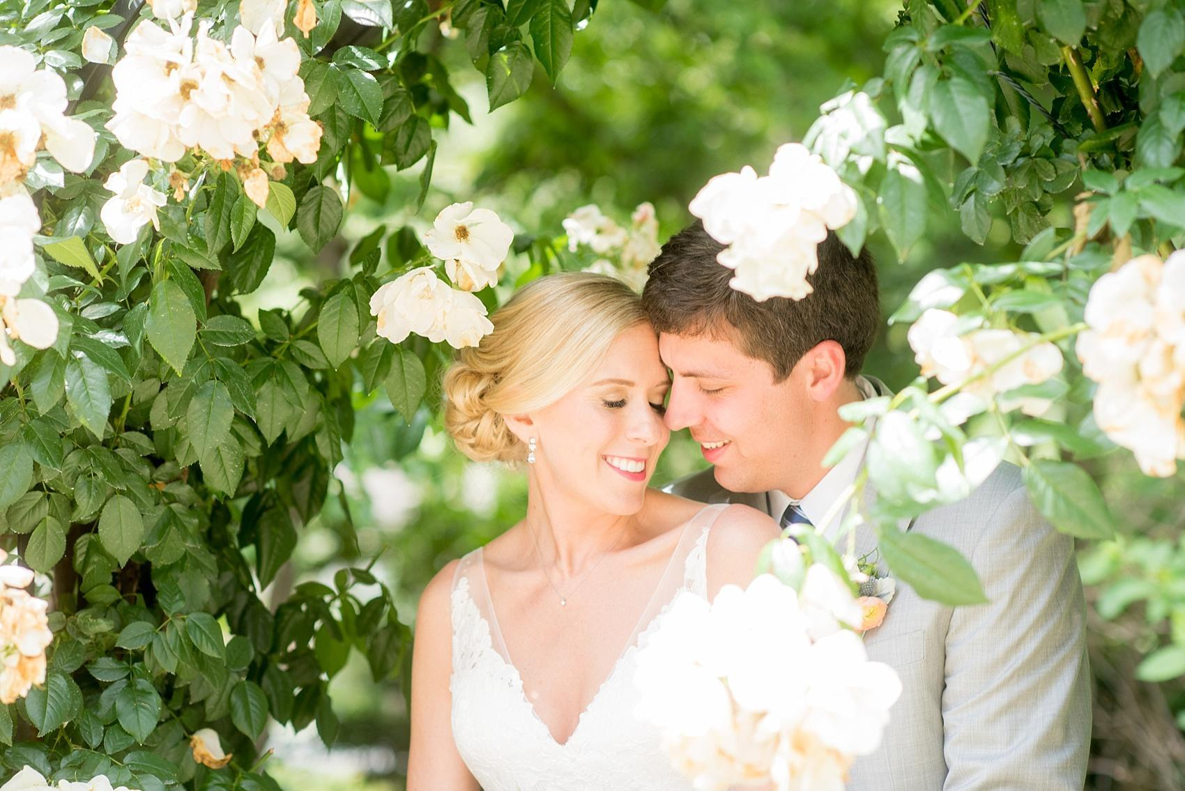 Mikkel Paige Photography photos of a downtown Raleigh Market Hall wedding with spring pictures of the bride and groom amidst rose bushes.