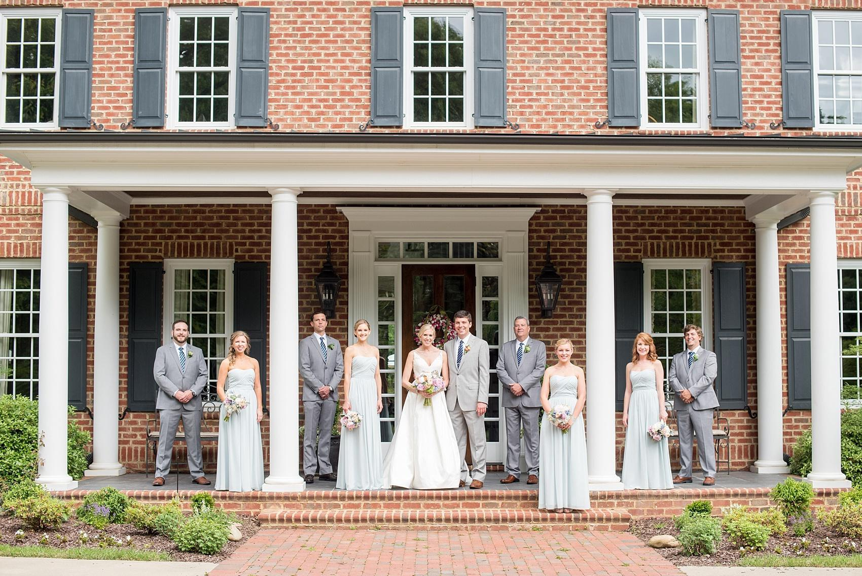 Mikkel Paige Photography photos of a downtown Raleigh Market Hall wedding with pictures of bridal party in blue gowns and groomsmen in grey suits. Wedding party on the porch!