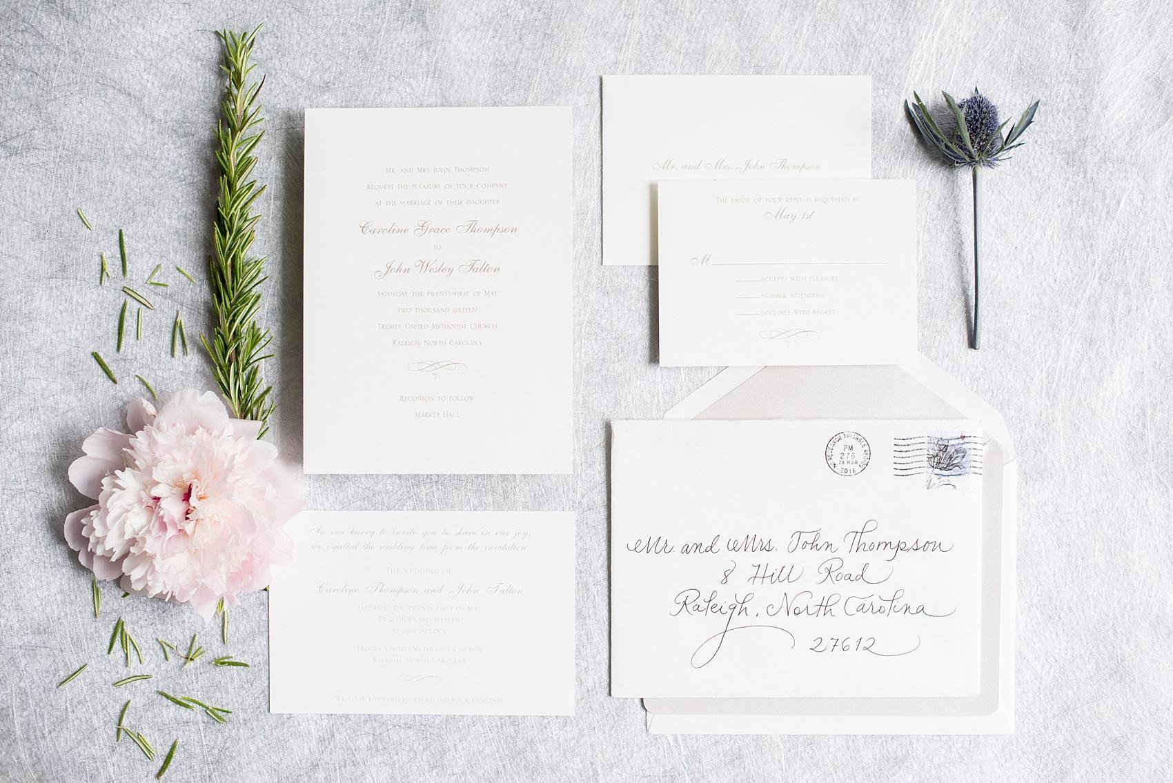 Mikkel Paige Photography photos of a downtown Raleigh Market Hall wedding with pictures of the simple white and silver invitation and custom envelope from If It's Paper and Calligraphy by Carrie.