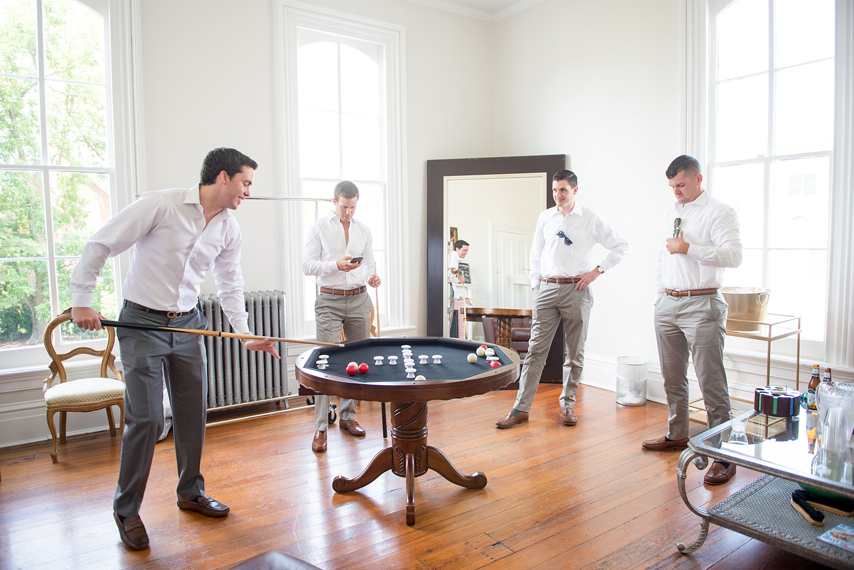 Mikkel Paige Photography wedding photos at The Merrimon-Wynne House in downtown Raleigh. The groom and his groomsmen relax and play table pool before the ceremony.