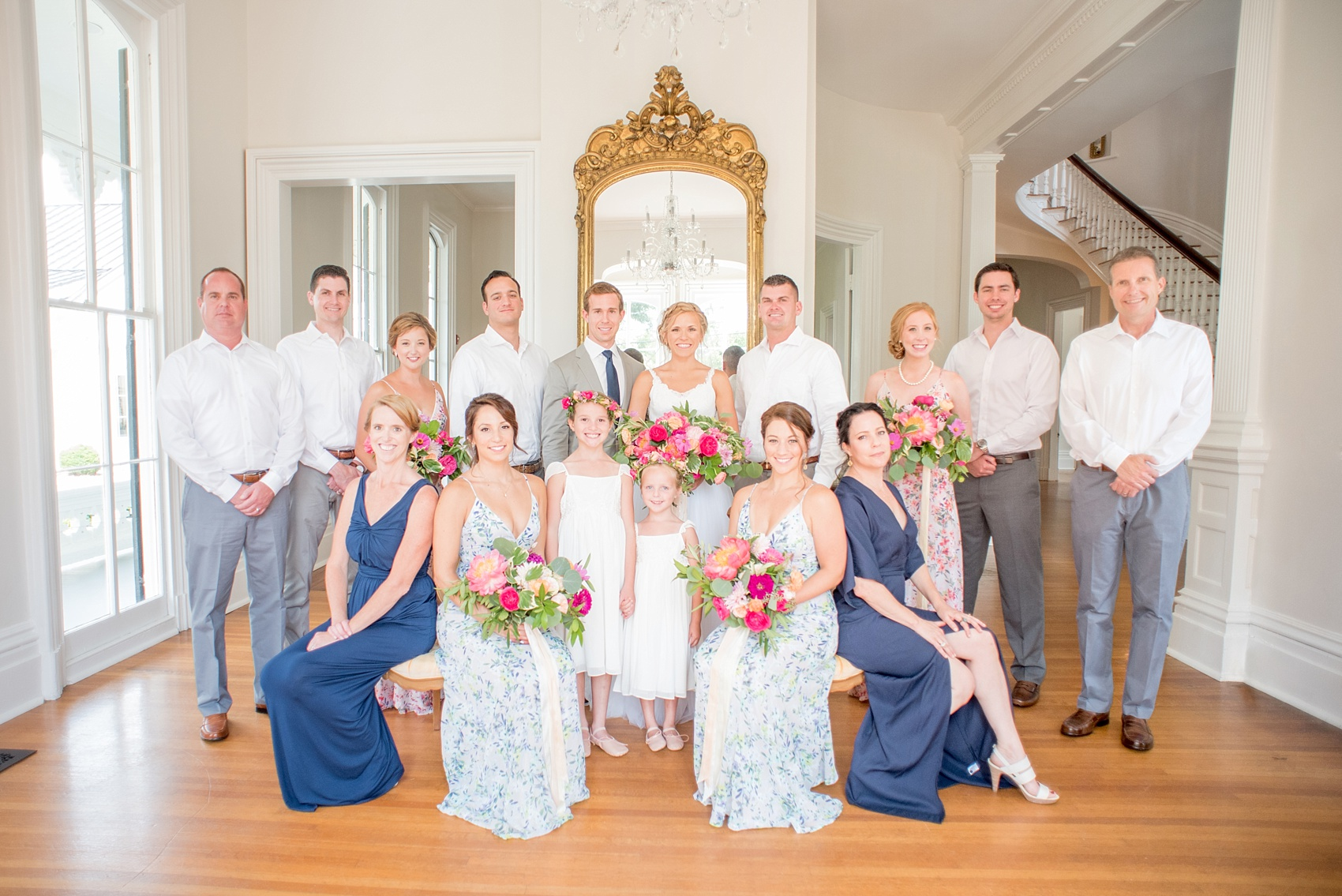 Mikkel Paige Photography wedding photos at The Merrimon-Wynne House in downtown Raleigh. A complete wedding party photo with bridesmaids in floral gowns and the groom's sisters in navy blue dresses.