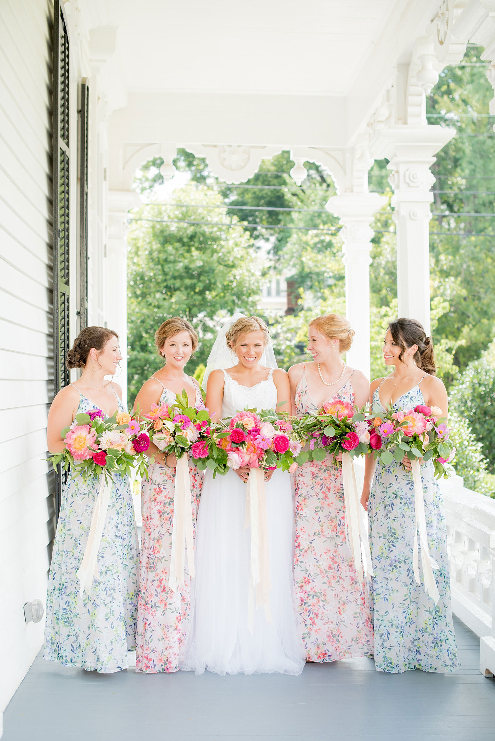 Mikkel Paige Photography wedding photos at The Merrimon-Wynne House in downtown Raleigh. Bridesmaids in floral maxi gowns with colorful pink, orange and green bouquets with peonies, eucalyptus and garden roses by Meristem Floral.