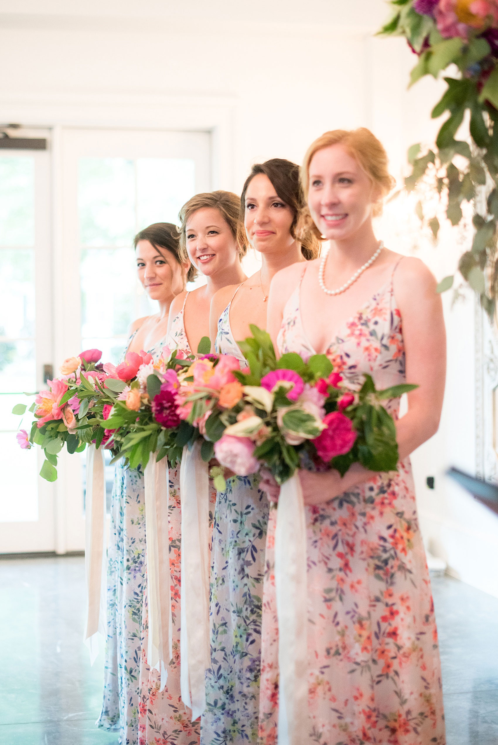 Mikkel Paige Photography wedding photos at The Merrimon-Wynne House in downtown Raleigh. The bridesmaids during the ceremony, pictured in floral maxi dresses with colorful bouquets.