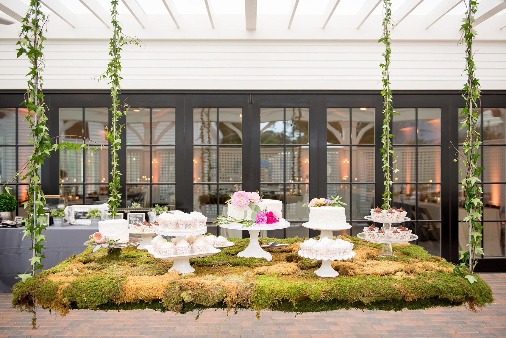 Mikkel Paige Photography wedding photos at The Merrimon-Wynne House in downtown Raleigh. A picture of the moss covered dessert table with multiple white cake and cupcakes.