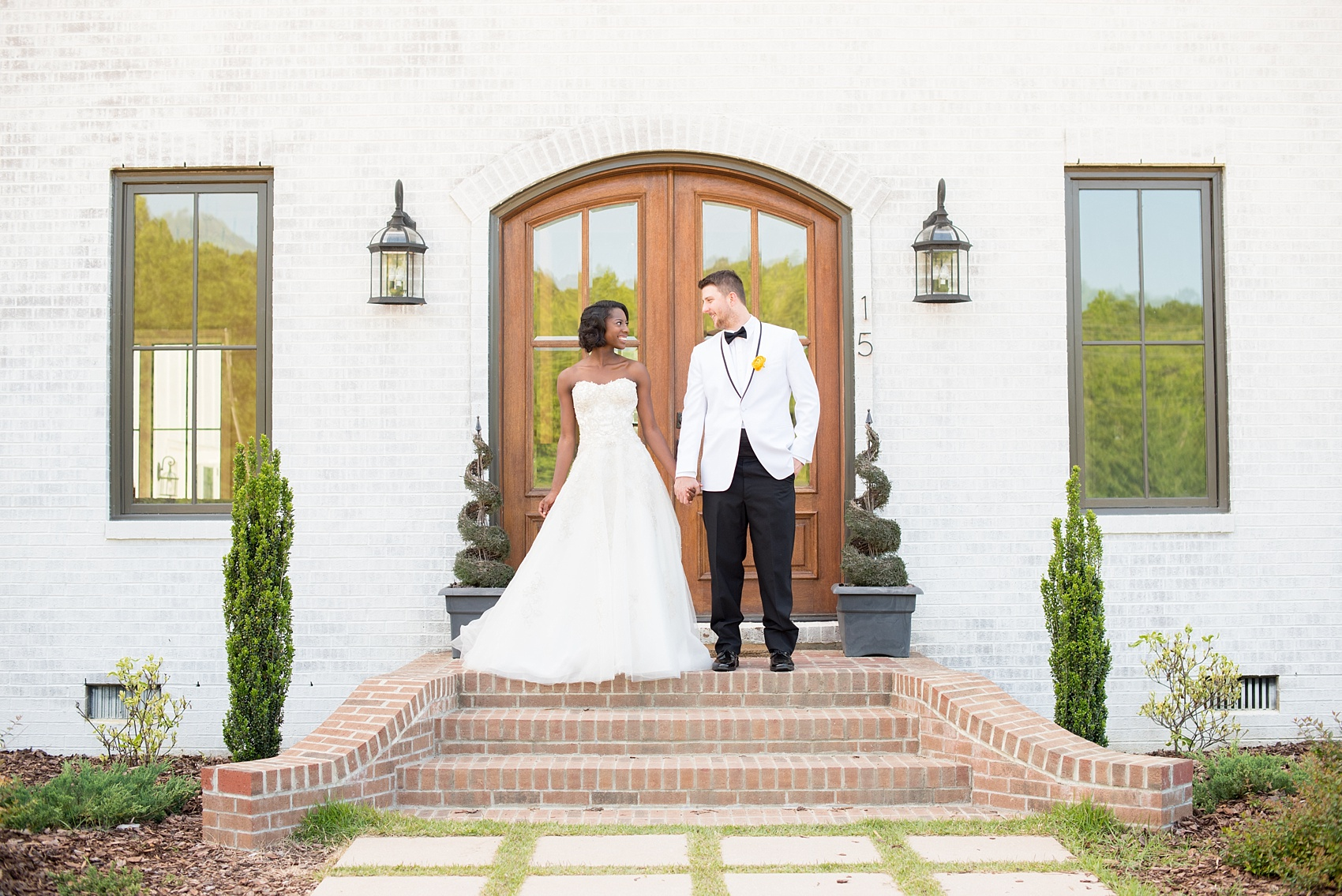 Mikkel Paige Photography photo at The Bradford, NC. Bride and groom of mixed race on the steps of the elegant NC home.