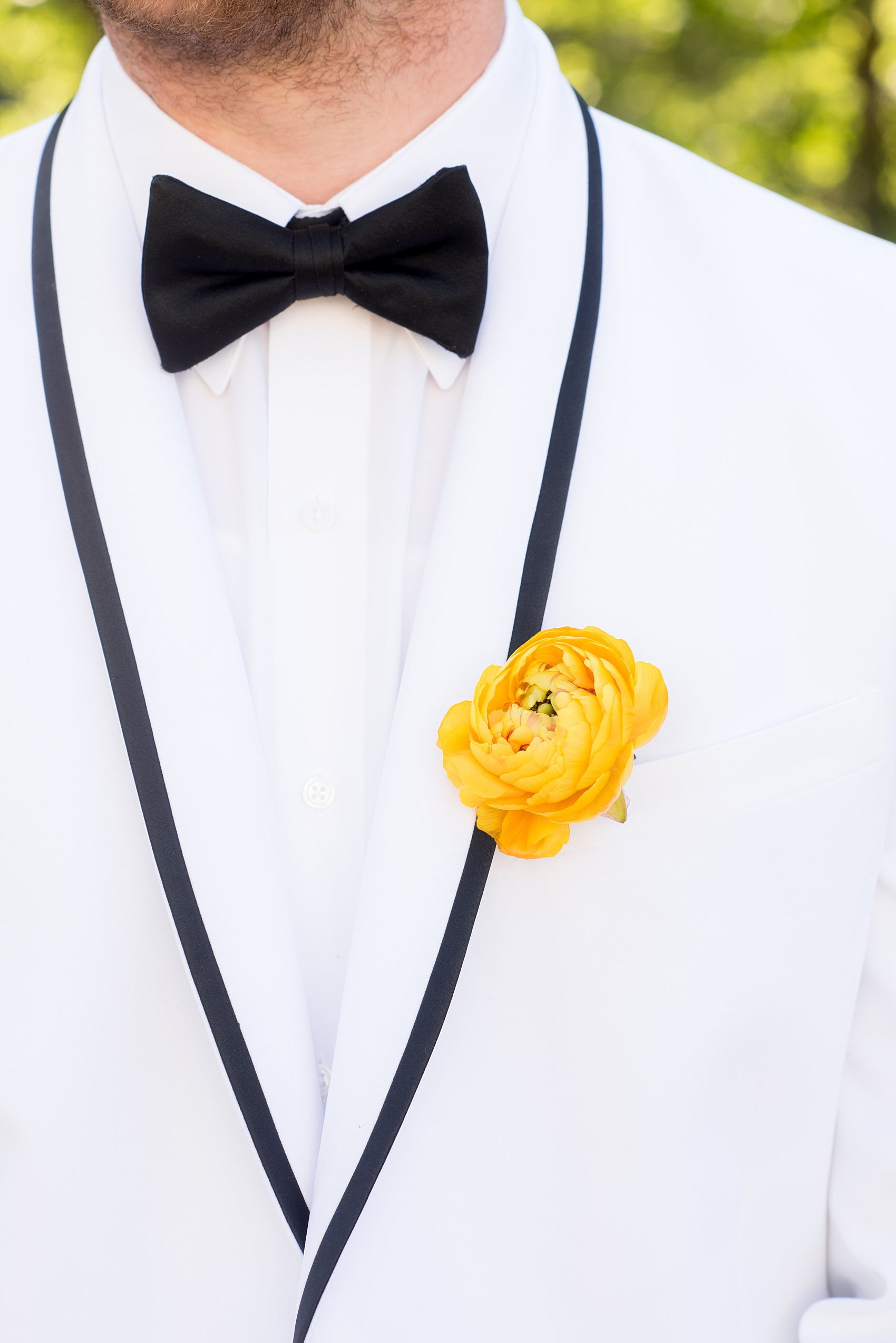 Mikkel Paige Photography wedding photo at The Bradford, NC. Groom in a white tuxedo suite jacket with black edge detail and a yellow ranunculus boutonniere alternative.