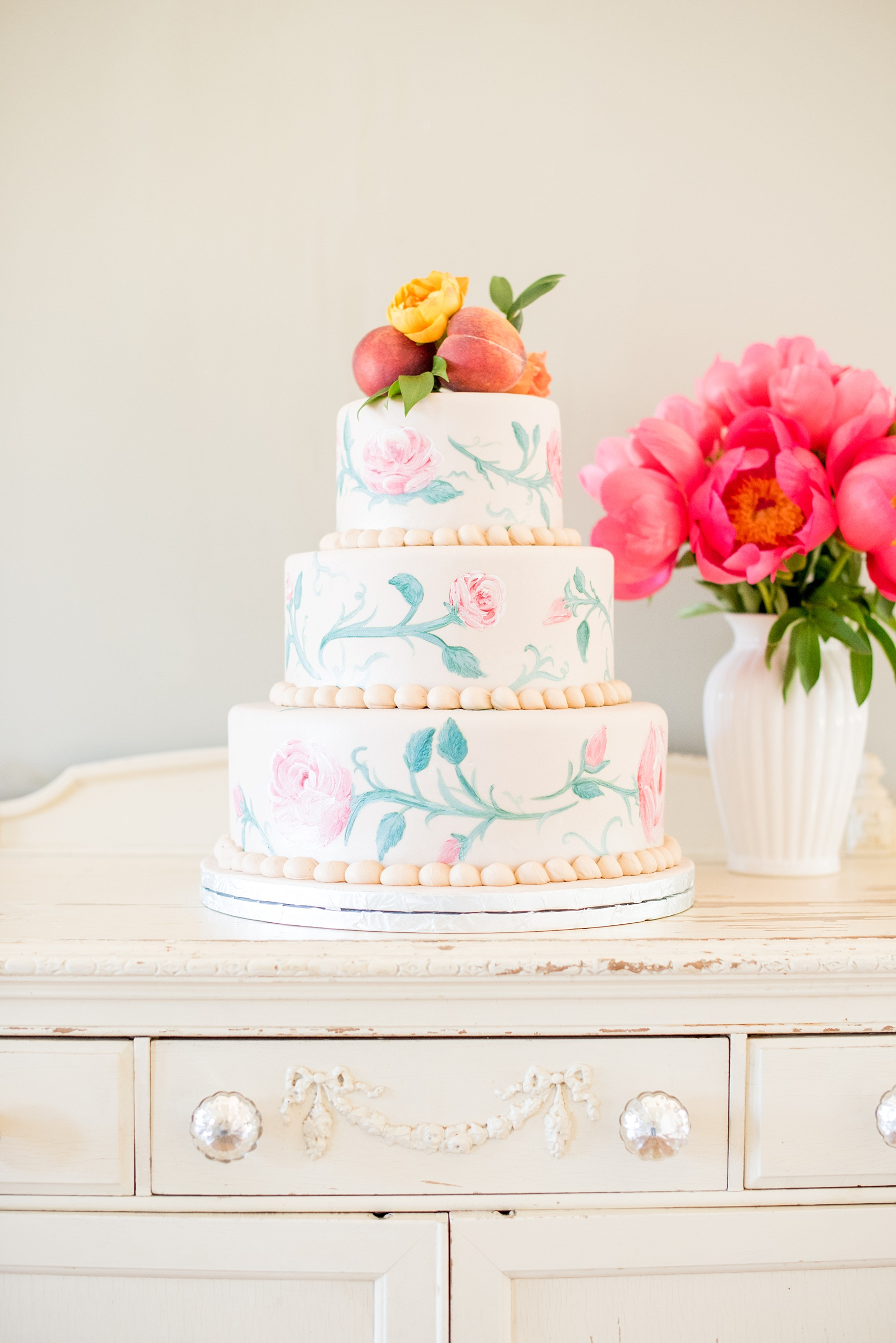 Mikkel Paige Photography photo at The Bradford, NC. Edible art tiered wedding cake in ivory fondant and hand painted pink roses and vines, topped with peaches and yellow ranunculus flower.