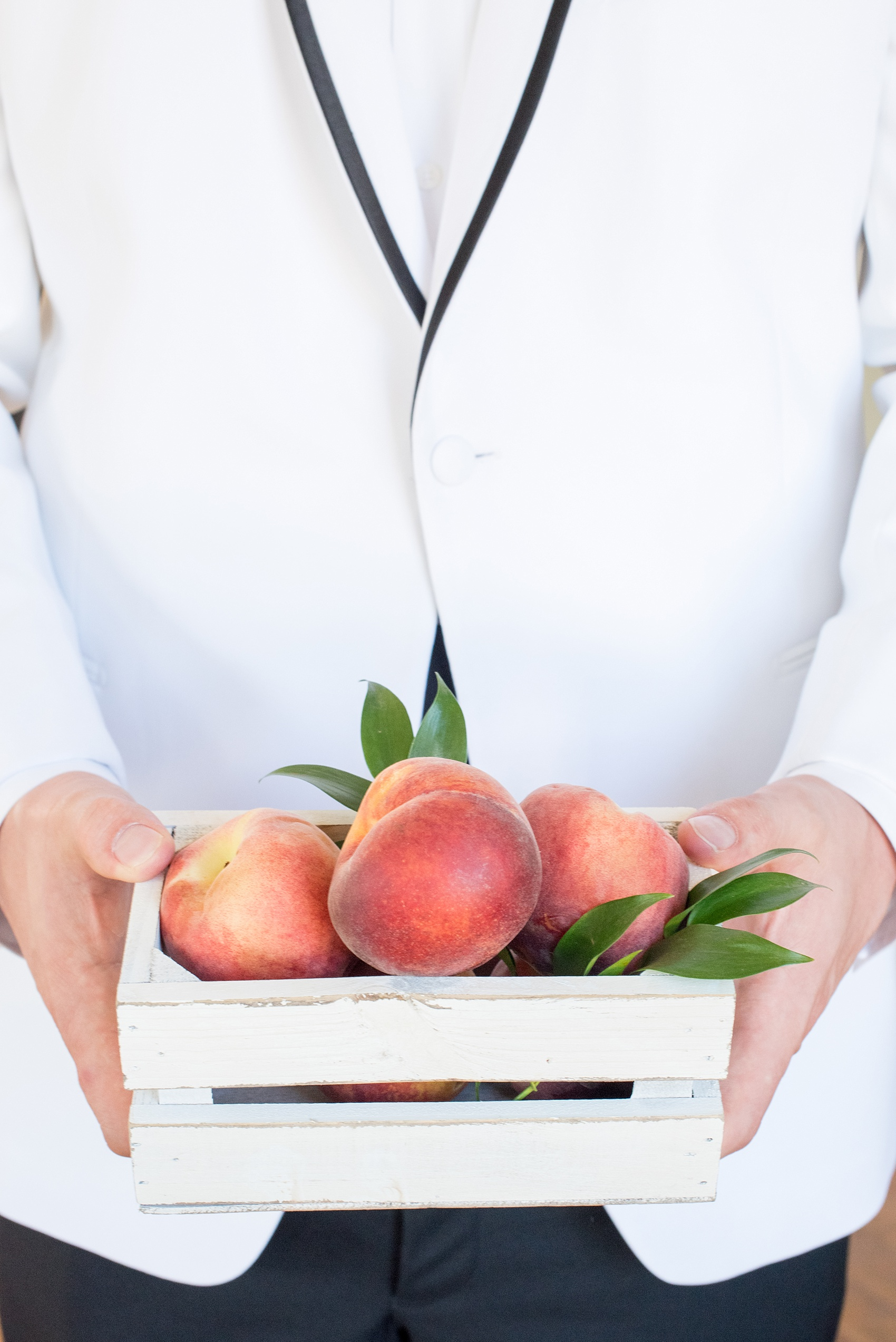 Mikkel Paige Photography wedding photo at The Bradford, NC. The groom holds a white shabby chic box of peaches.