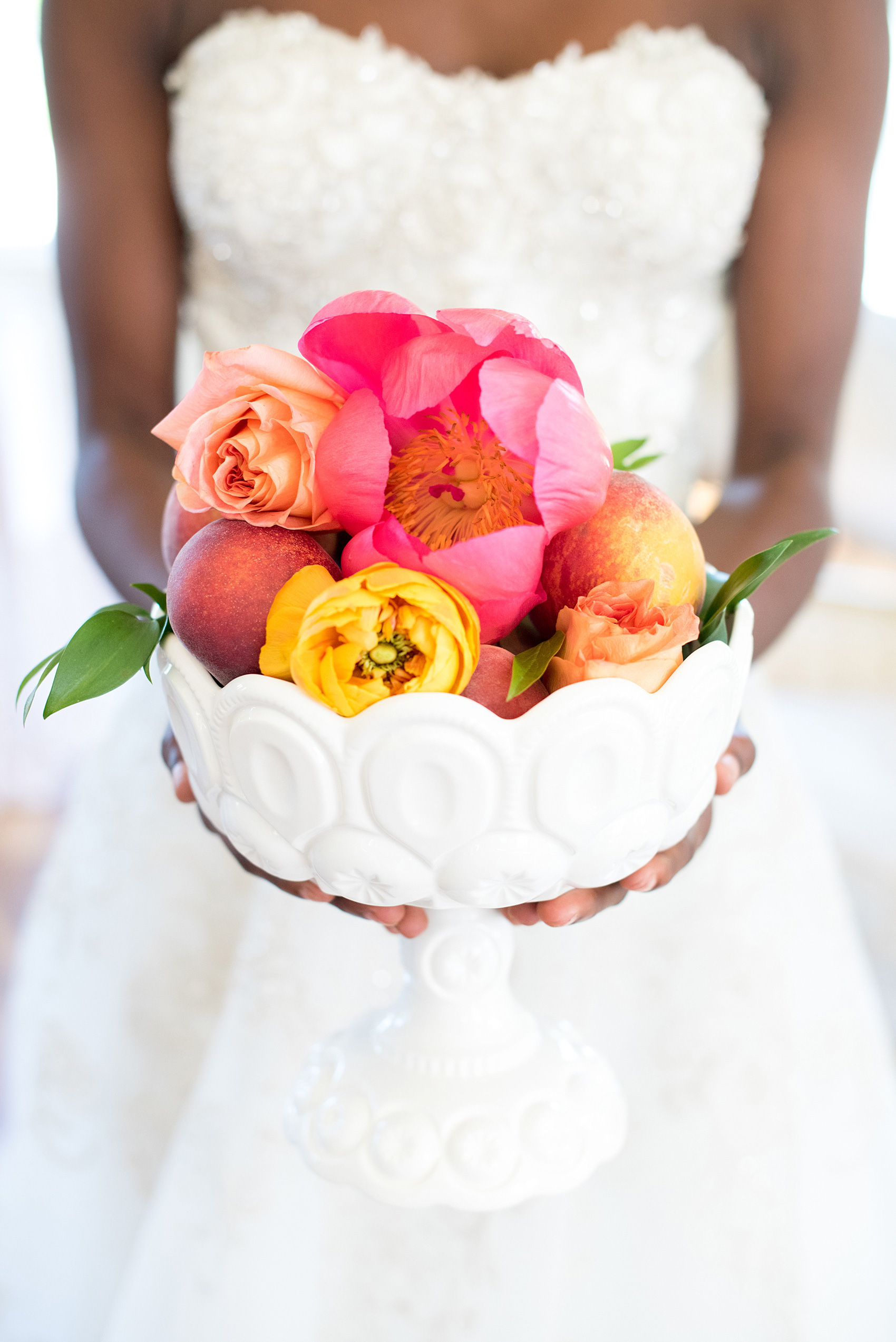 Mikkel Paige Photography photo at The Bradford, NC. Bride holding a milk glass vase full of pink peonies, yellow ranunculus and peaches.