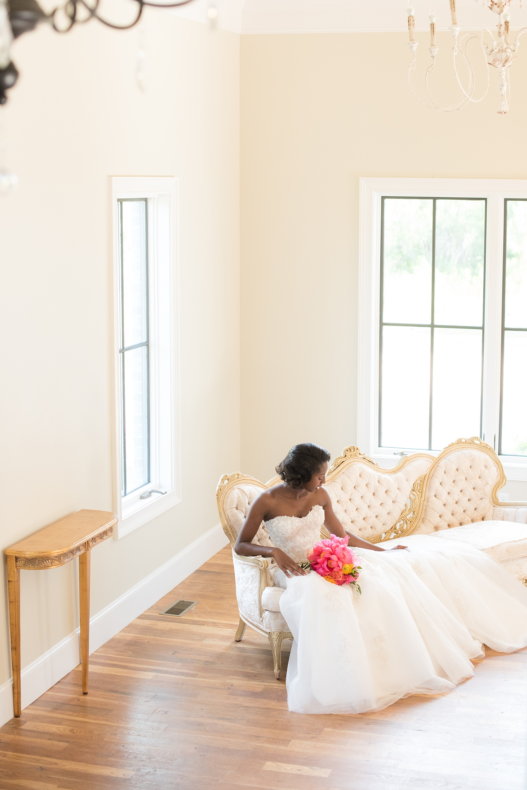 Mikkel Paige Photography photo at The Bradford, NC. Bride on an ivory sofa inside the elegant NC home.
