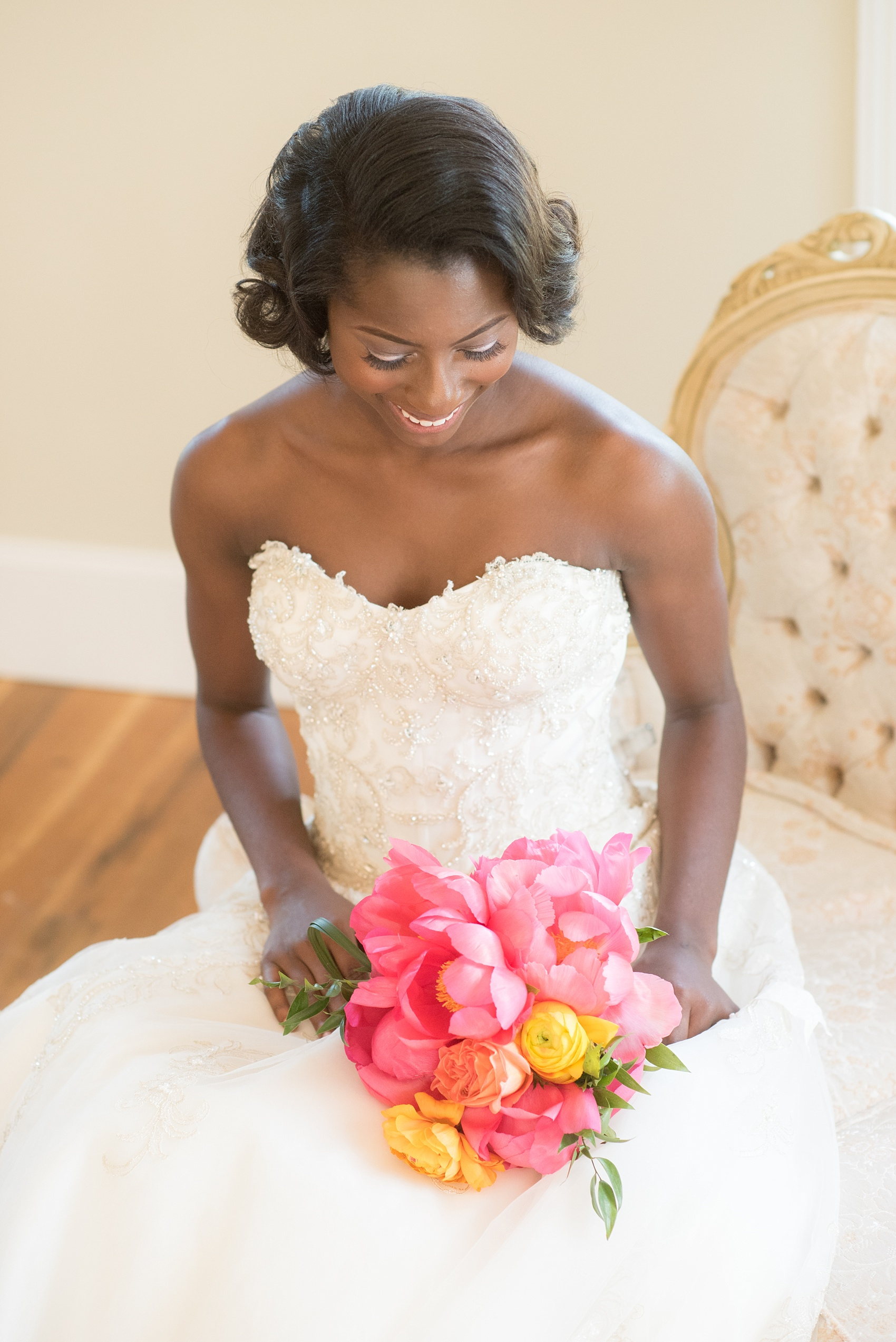 Mikkel Paige Photography photo at The Bradford, NC. Bride in a strapless gown on an ivory sofa inside the elegant NC home.