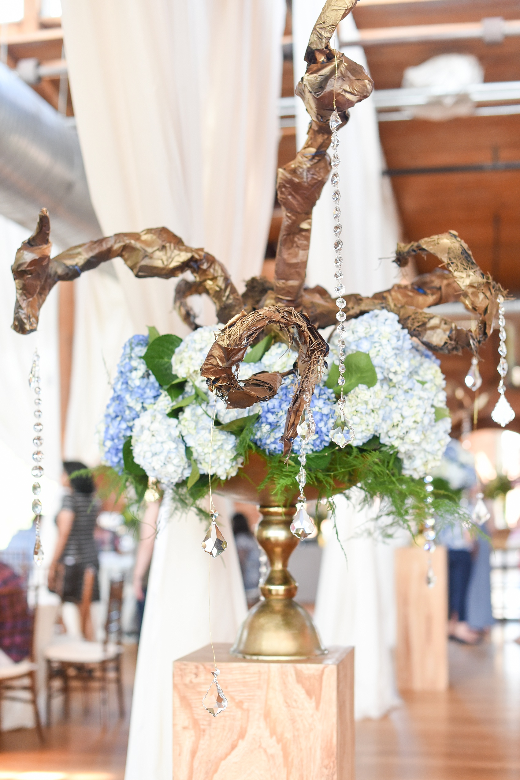 Mikkel Paige Photography photos from The Cotton Room wedding venue in Durham, NC. A beautiful floral centerpiece with greenery and blue hydrangea and crystals hanging off.