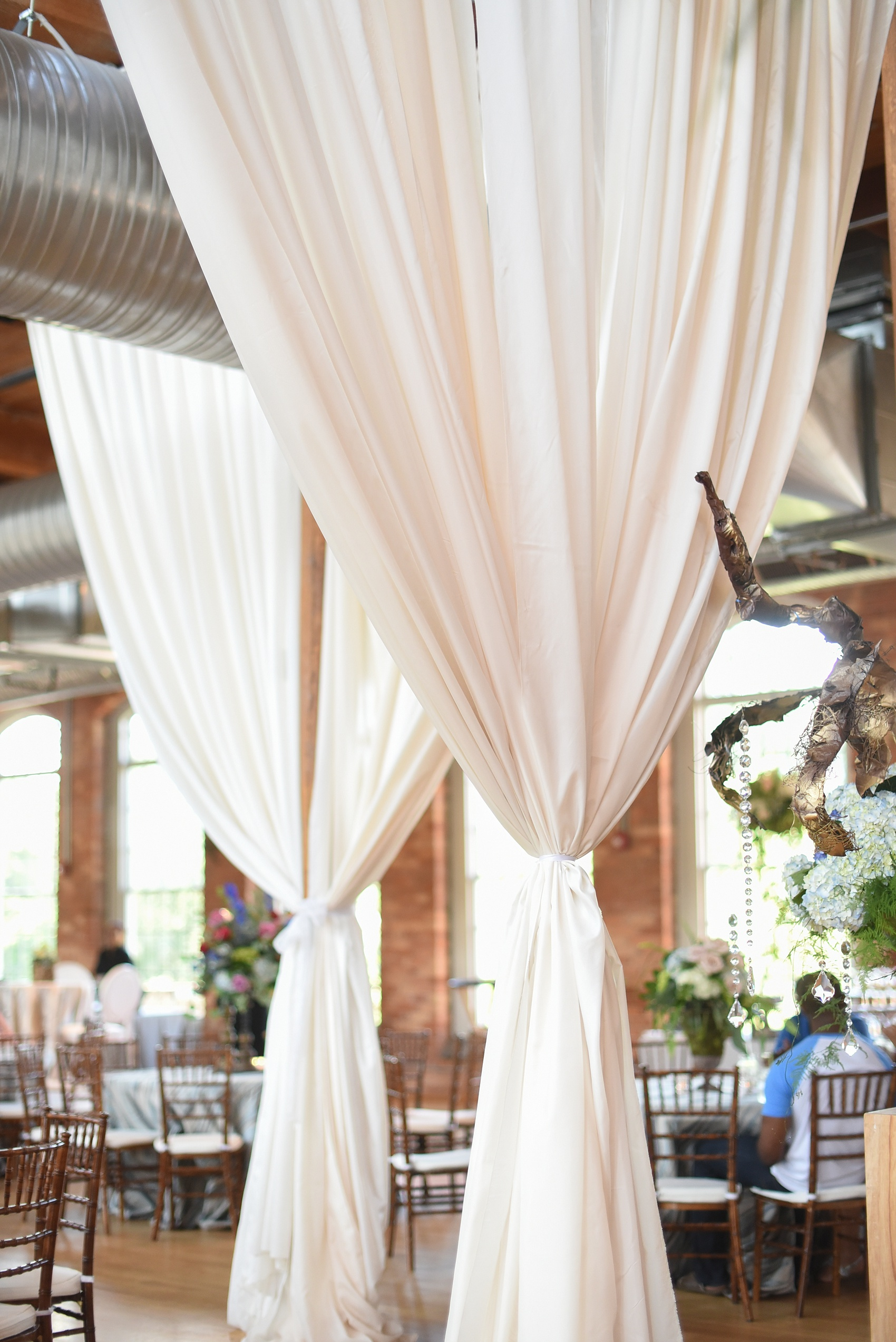Mikkel Paige Photography photos from The Cotton Room wedding venue in Durham, NC. Cotton linen draped from the ceiling rafters served as elegant room dividers and accents.