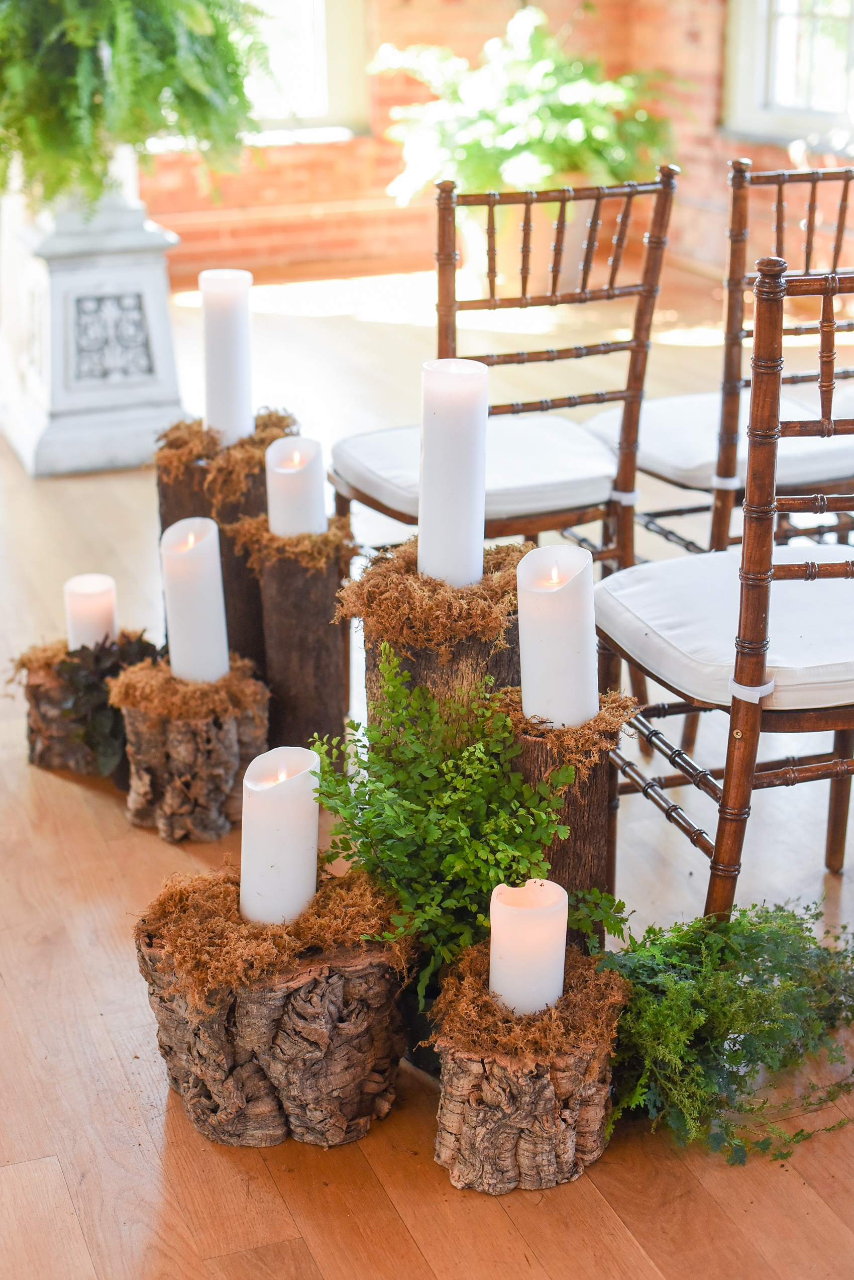 Mikkel Paige Photography image from The Cotton Room wedding venue in Durham, NC. A wooden fairy forest scene of candles and wood tree trunk stumps with moss lined the ceremony aisle.