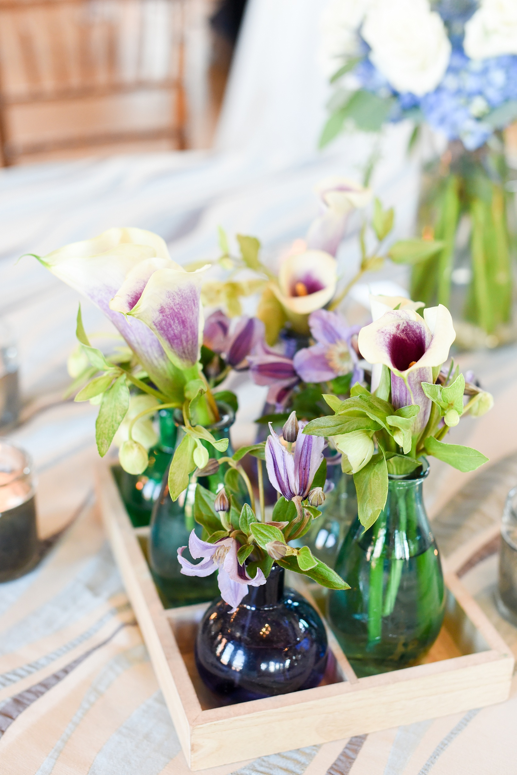 Mikkel Paige Photography image from The Cotton Room wedding venue in Durham, NC. Fresh flowers in bud vases of varying blue shades sat in a rustic wooden tray container. Picasso calla lilies and helleborus flowers completed the look.