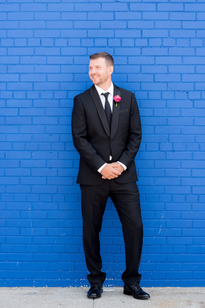Mikkel Paige Photography photo of Dobbin St Brooklyn wedding. Planning and coordination by Color Pop Events. Tuxedo from The Black Tux for the groom, image against a colorful blue wall.