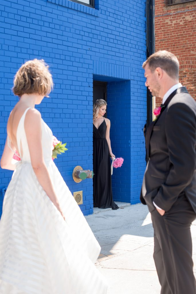 Mikkel Paige Photography photo of Dobbin St Brooklyn wedding. Planning and coordination by Color Pop Events. Tuxedo from The Black Tux for the groom, image against a colorful blue wall. Bride in a Hayley Paige white striped gown and bridesmaid in a black dress.