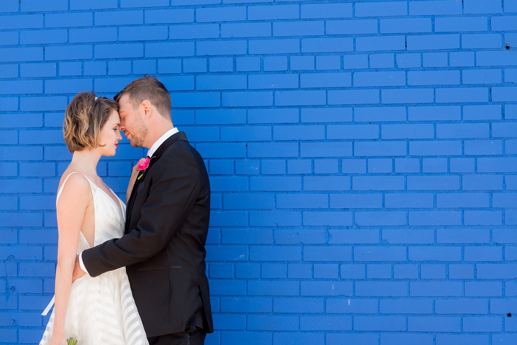 Mikkel Paige Photography photo of Dobbin St Brooklyn wedding. Planning and coordination by Color Pop Events. Tuxedo from The Black Tux for the groom, image against a colorful blue wall. Bride in a Hayley Paige white striped gown.