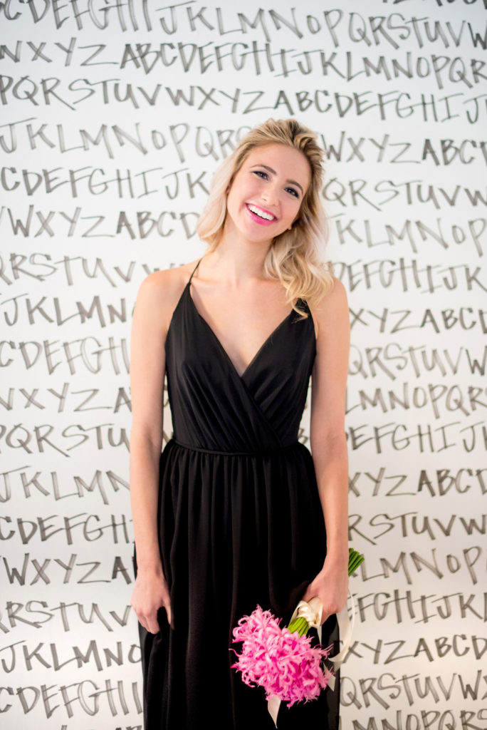 Mikkel Paige Photography photo of Dobbin St Brooklyn wedding. Planning and coordination by Color Pop Events. Black chiffon bridesmaid gown by Hayley Paige Occasions. Image against black and white alphabet wallpaper by Sarah Merenda.
