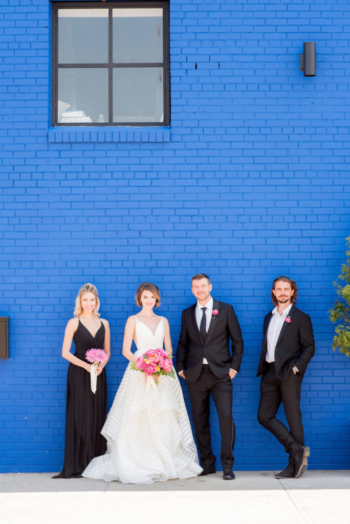 Mikkel Paige Photography photo of Dobbin St Brooklyn wedding. Planning and coordination by Color Pop Events. Classic wedding party in black and white against a colorful blue wall. Bride in Hayley Paige white striped gown with short hair do with headband detail. Peony and ranunculus bouquet by Blade NYC.