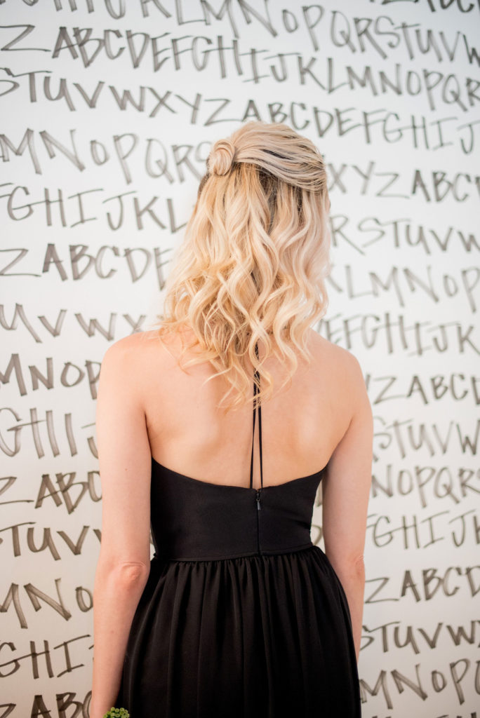 Mikkel Paige Photography photo of Dobbin St Brooklyn wedding. Planning and coordination by Color Pop Events. Black chiffon bridesmaid gown by Hayley Paige Occasions. Image against black and white alphabet wallpaper by Sarah Merenda. Hair do in a half up bun.