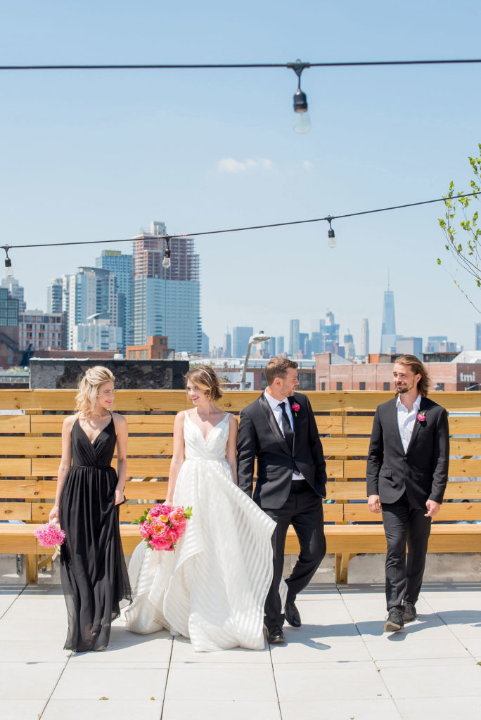 Mikkel Paige Photography photo of Dobbin St Brooklyn wedding. Planning and coordination by Color Pop Events. Rooftop photos in Williamsburg with the Empire State Building and Freedom Tower behind the bridal party.