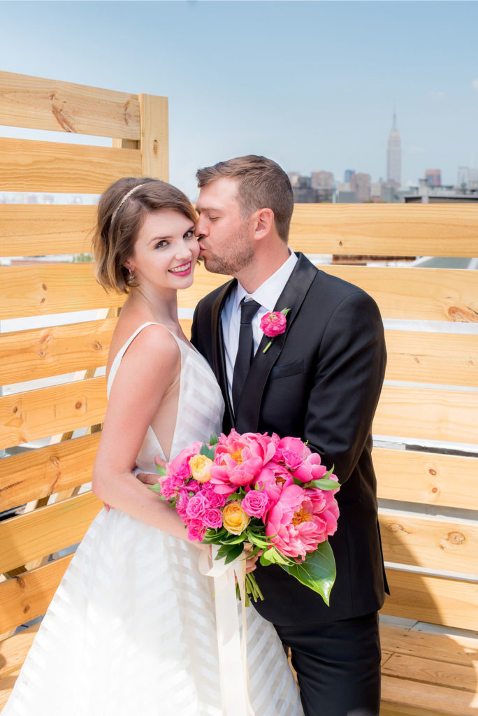 Mikkel Paige Photography photo of Dobbin St Brooklyn wedding. Planning and coordination by Color Pop Events. Rooftop photos in Williamsburg with the Empire State Building and Freedom Tower behind the bride and groom.