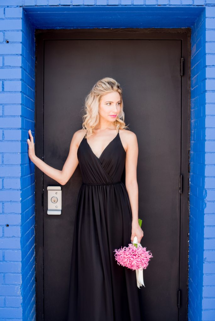 Mikkel Paige Photography photo of Dobbin St Brooklyn wedding. Planning and coordination by Color Pop Events. Black chiffon bridesmaid gown by Hayley Paige Occasions. Image against a bright blue and black. Hair do in a half up bun.