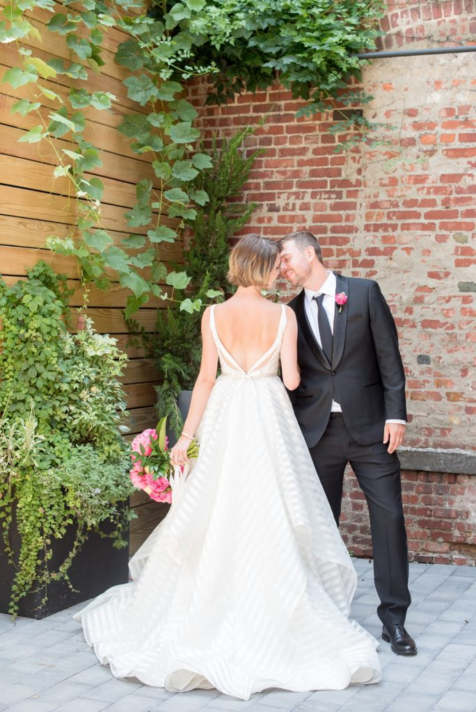 Mikkel Paige Photography photo of Dobbin St Brooklyn wedding. Planning and coordination by Color Pop Events. Bride in a white striped Hayley Paige gown and groom in classic Tuxedo by The Black Tux. Outdoor patio image against greenery and rustic brick.