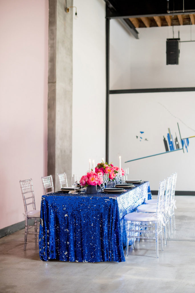 Mikkel Paige Photography photo of Dobbin St Brooklyn wedding. Planning and coordination by Color Pop Events. Reception table with blue sequins, pink peony centerpieces and clear chiavari chairs.