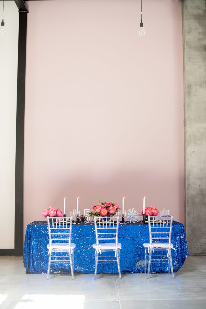 Mikkel Paige Photography photo of Dobbin St Brooklyn wedding. Planning and coordination by Color Pop Events. Reception table with blue sequins, pink peony centerpieces and clear chiavari chairs against a mauve wall.