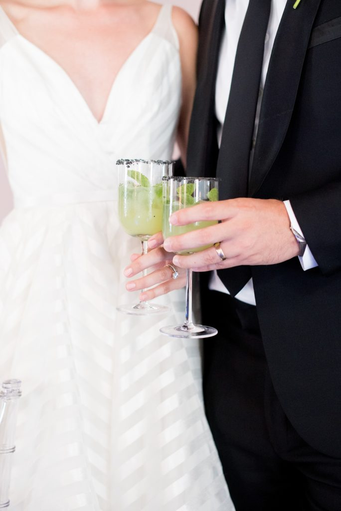 Mikkel Paige Photography photo of Dobbin St Brooklyn wedding. Planning and coordination by Color Pop Events. Reception toast cheers with the bride and groom drinking a custom cucumber cocktail.