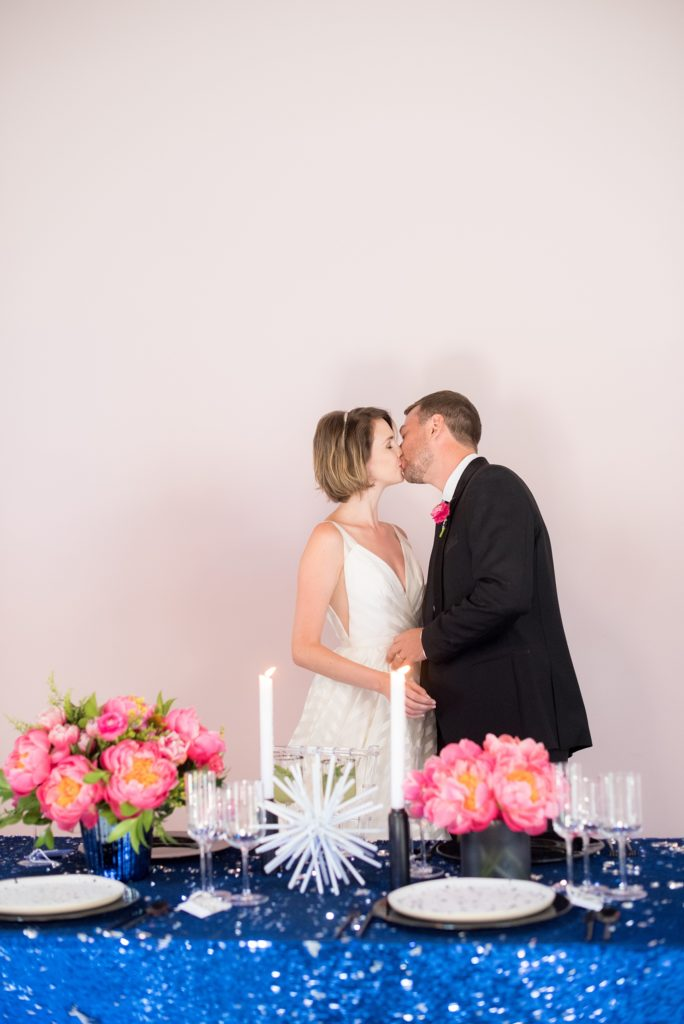 Mikkel Paige Photography photo of Dobbin St Brooklyn wedding. Planning and coordination by Color Pop Events. Reception table with blue sequins, pink peony centerpieces and clear chiavari chairs against a mauve wall with the bride and groom.
