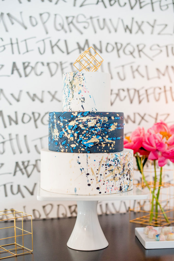 Mikkel Paige Photography photo of Dobbin St Brooklyn wedding. Planning and coordination by Color Pop Events. Colorful navy, gold and silver splatter painted dessert by Nine Cakes with a geometric topper.