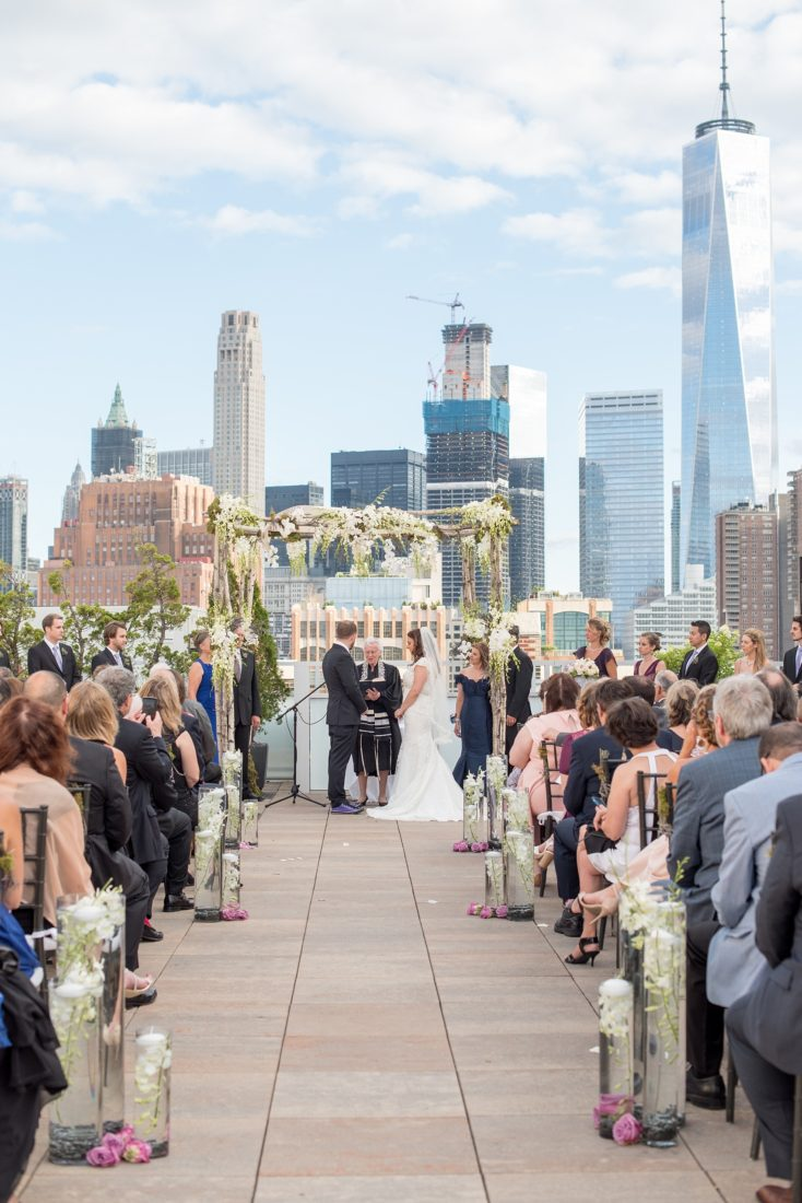 Mikkel Paige Photography photos of a NYC wedding at Tribeca Rooftop. An image of the outdoor ceremony with Freedom Tower in the background.
