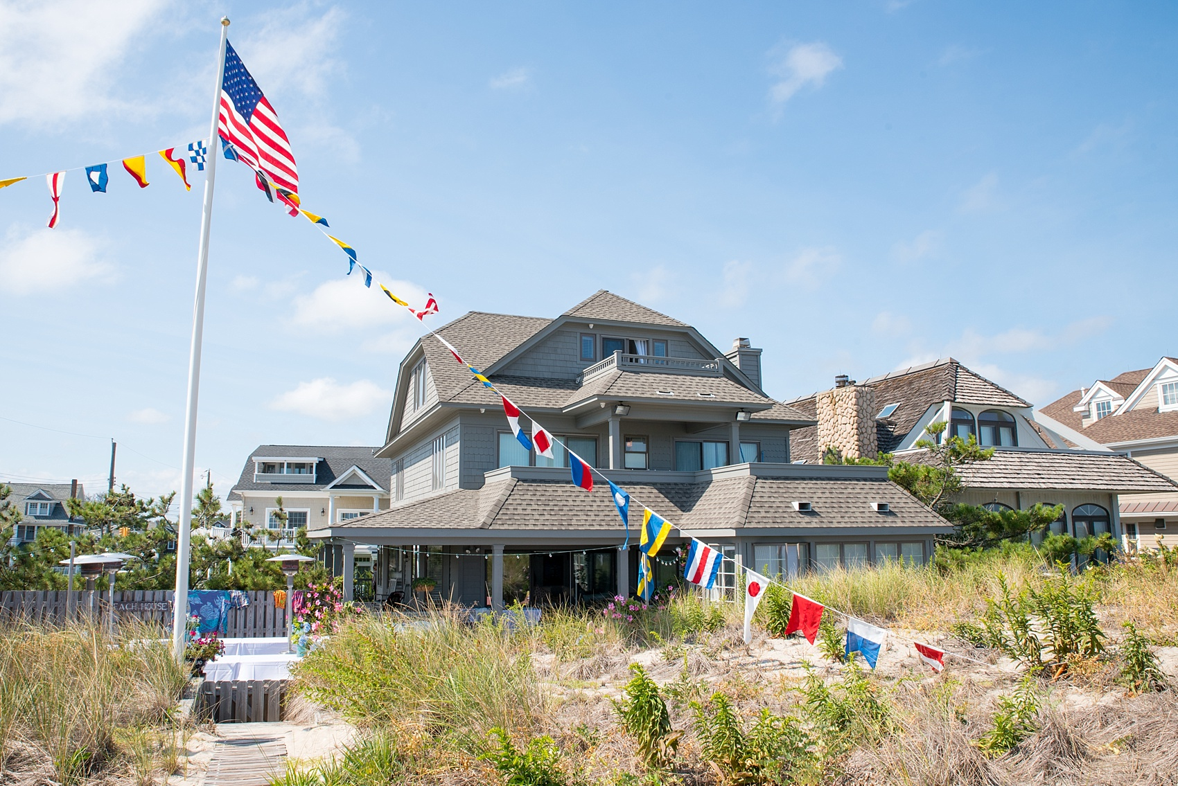Mikkel Paige Photography photos from a Bay Head Yacht Club wedding in NJ. The groom prepared at his parents beach house complete with nautical flags.