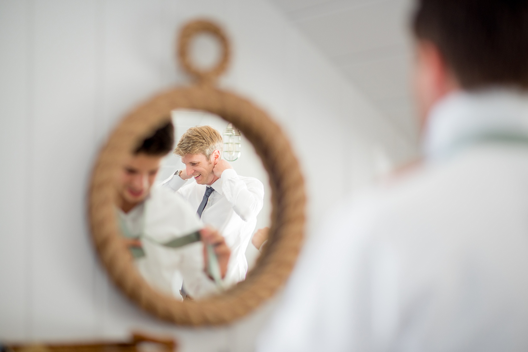 Mikkel Paige Photography photos from a Bay Head Yacht Club wedding in NJ. The groom prepared at his parents beach house in a nautical themed room with a sea rope mirror.