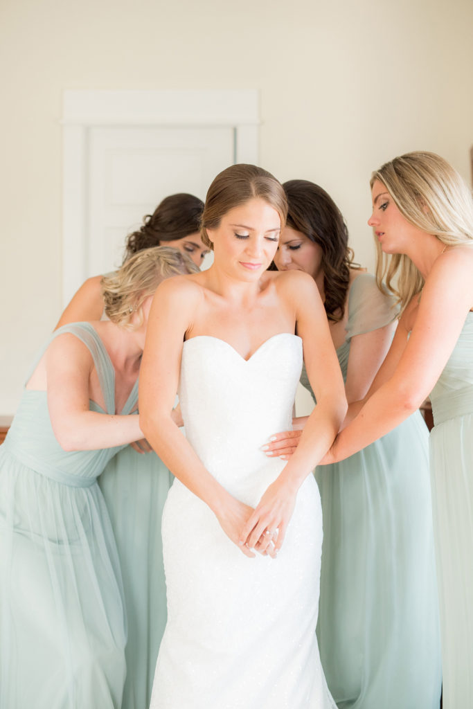 Mikkel Paige Photography photo of a wedding in Bay Head, NJ. The bridesmaids help the bride get ready in mint green chiffon gowns.