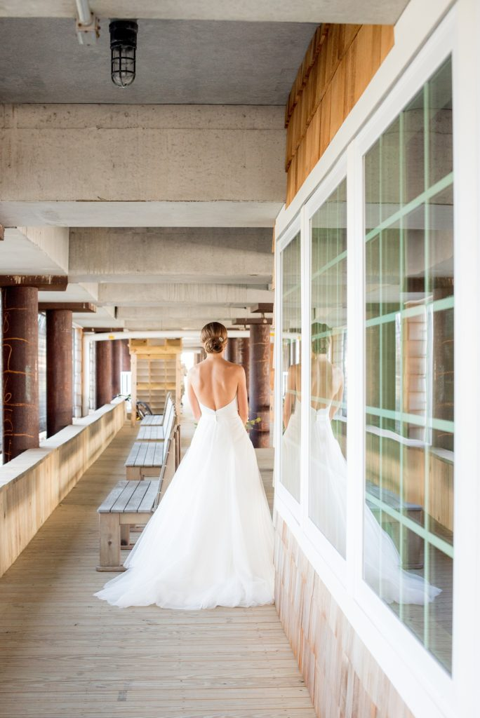 Mikkel Paige Photography photos of a Bay Head Yacht Club nautical wedding. The bride wore a low back sweetheart neckline gown from Kleinfeld and a low bun hari do. We caught her reflection in the window of this unique image as she walked towards the groom for their first look.