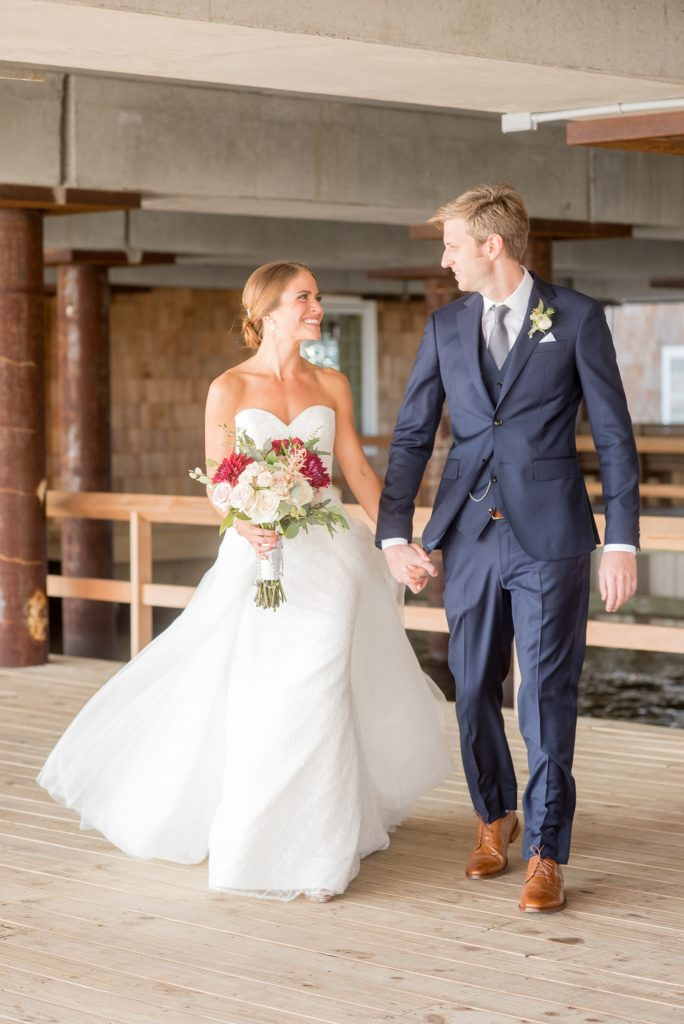 Mikkel Paige Photography photos of a Bay Head Yacht Club nautical wedding. The bride wore a tulle overlay for a second look with her white sweetheart neckline gown and the groom wore a navy blue three-piece suit.
